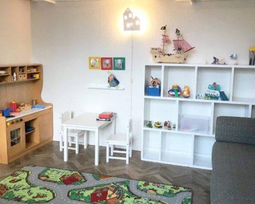 Børneværelse med legesager, en sofa og et lille bord med stole